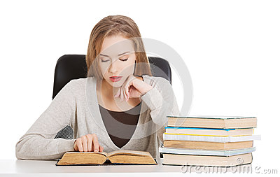 Beautiful casual student woman sitting by stack of books and lea