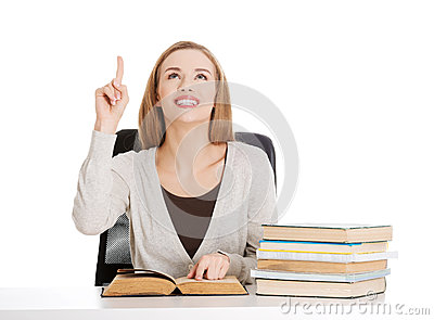 Beautiful casual student woman sitting by stack of books and poi