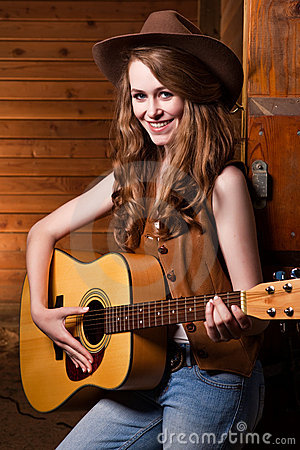 Beautiful caucasian cowgirl with guitar