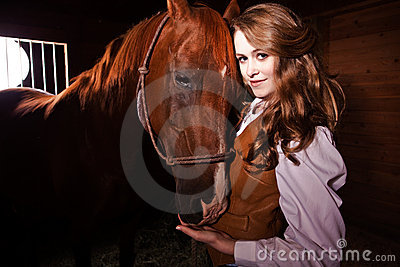 Beautiful caucasian cowgirl with a horse