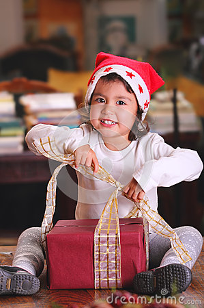 Beautiful child opens christmas gifts