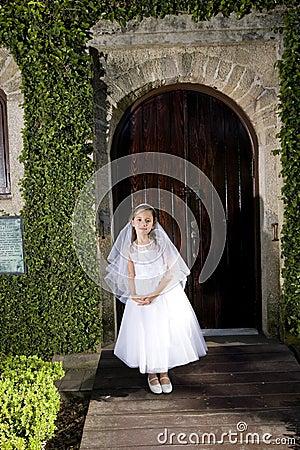 Beautiful child in white dress outside chapel door