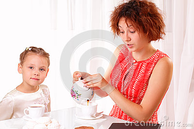 Beautiful child and young girl drinking tea