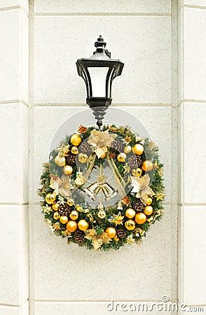 Christmas wreath on lantern on white wall royalty free stock image
