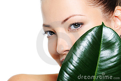 Beautiful clean woman s face behind the leaf