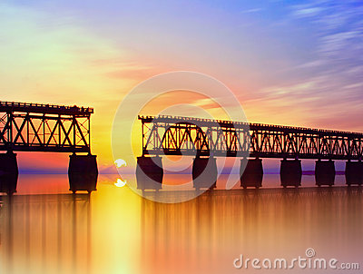 Beautiful colorful sunset or sunrise with broken bridge and cloudy sky