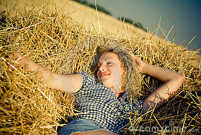 Beautiful country girl lying on the haystack