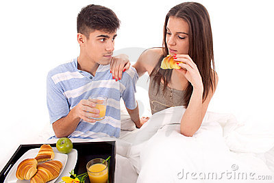 Beautiful couple having breakfast lying in the bed