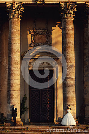 Free Beautiful Couple In Wedding Dress Outdoors Near The Vintage Portal Entrance With Columns Stock Photography - 64302902