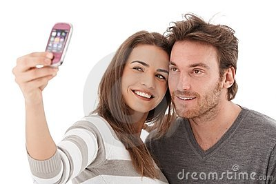 Beautiful couple photographing themselves smiling