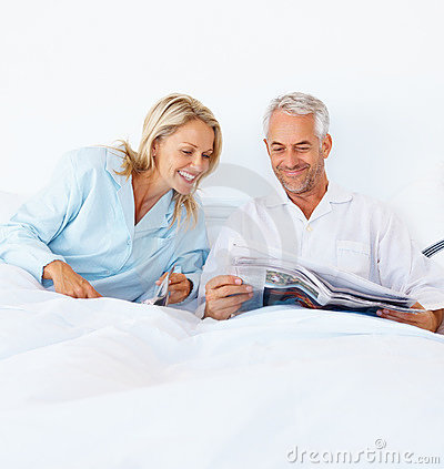 A beautiful couple reading newspaper in bed