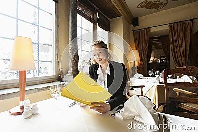 Beautiful customer reading menu at restaurant table