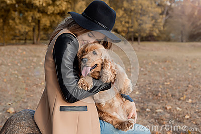 Beautiful cute happy girl in a black hat playing with her dog in a park Stock Photo