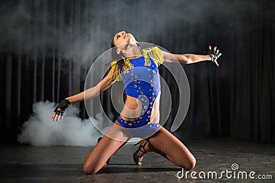 Beautiful dancer girl in a blue costume sitting
