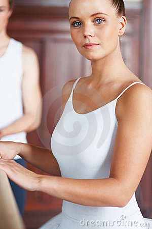 Beautiful dancer holding ballet bar with trainer