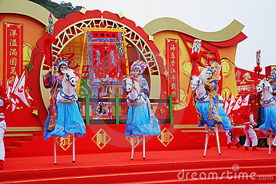 Beautiful dancers on stilts represent horsemen Editorial Stock Photo