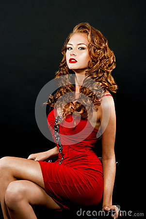 Beautiful, daring red-haired girl in a red dress