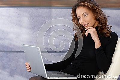 Beautiful ethnic female using laptop computer