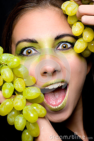 Beautiful excited woman holding green grapes