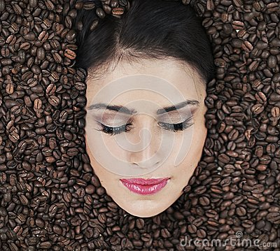 Beautiful face among coffe beans