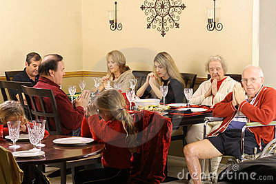 Beautiful family praying at breakfast
