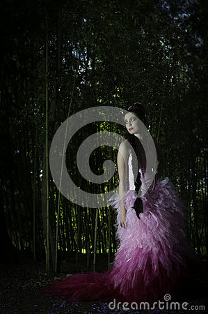 Beautiful fantasy woman in pink evening dress standing in enchanted forest looking back over her shoulder