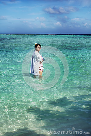 Beautiful fashion asian girl plays water in ocean