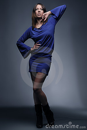 Beautiful fashion model in blue on dark background
