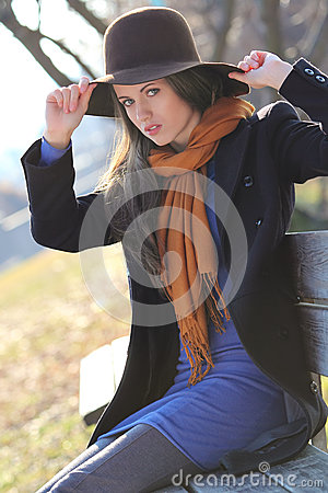 Beautiful fashion model poses on a bench