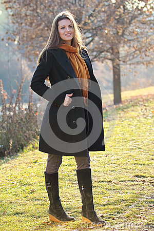 Beautiful fashion model poses outdoor in the park