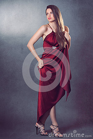 Beautiful fashion model posing in elegant red dress