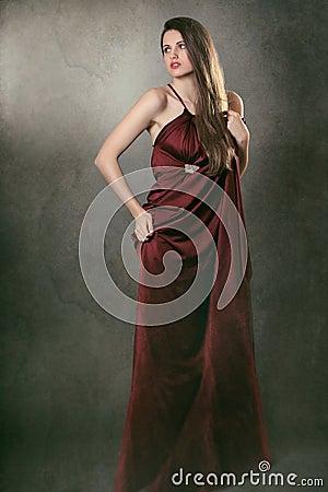Beautiful fashion model posing in elegant red dress