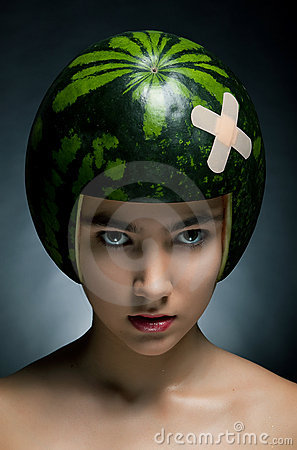Beautiful fashion model with watermelon as hardhat