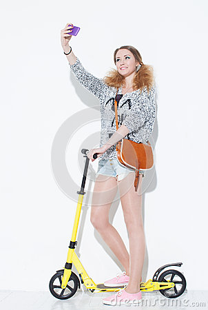 Free Beautiful Fashionable Blonde Girl Taking A Crazy Fun Selfie With A Vintage Bag On His Shoulder. Standing On A Yellow Scooter. Clos Royalty Free Stock Photo - 48000135