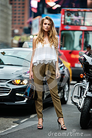 Free Beautiful Fashionable Woman Standing On City Street On Car Traffic Wearing Green Pants, White Sexy T-shirt And Holding Bag Stock Image - 74036761