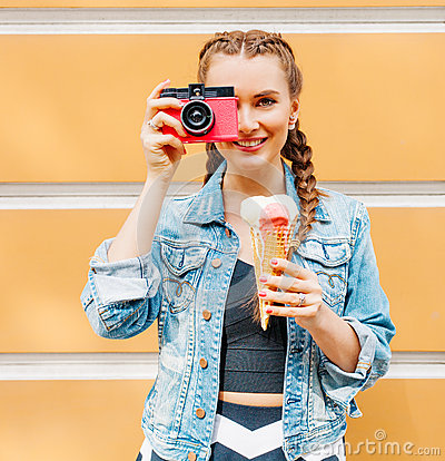 Beautiful fashionable young girl posing in a summer dress and denim jacket with pink vintage camera and multi-colored ice cream. T Stock Photo