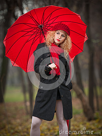 Beautiful fashionable young girl with red umbrella , red cap and red scarf in the park
