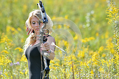 Beautiful female archer shoots an arrow