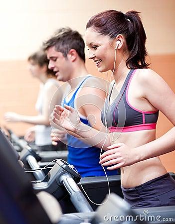 Beautiful female athlete standing on a treadmill