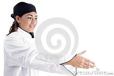 Beautiful female chef offering handshake