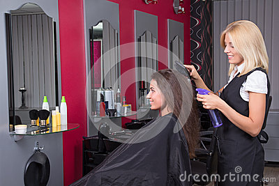Beautiful female hairdresser working in beauty salon