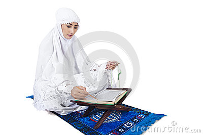 Beautiful female muslim reading Quran on white