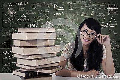 Beautiful female nerd student study in class
