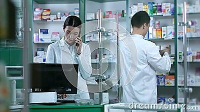 Beautiful female pharmacist taking orders on phone stock video