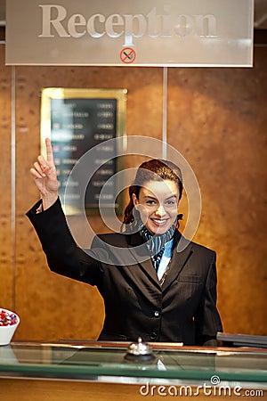 Beautiful female receptionist indicating upwards
