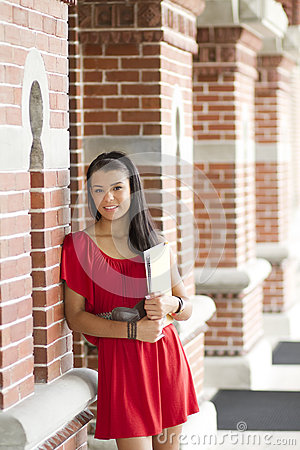 Beautiful female student leaning against a brick w