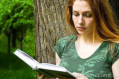 Beautiful female student reading in campus