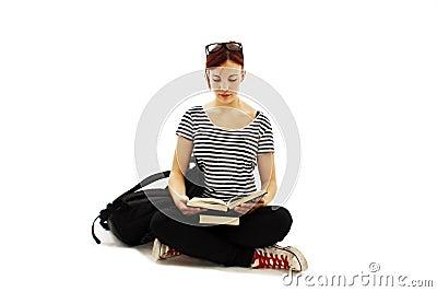 Beautiful female student sitting on floor studying