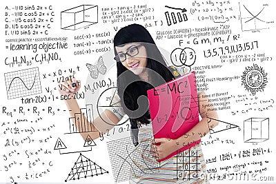 Beautiful female student write on transparent white board