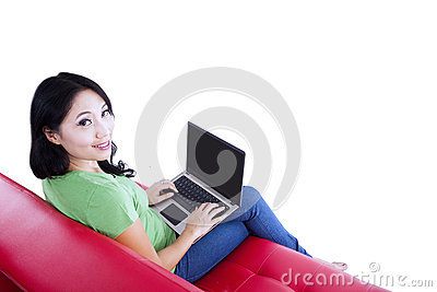 Beautiful female typing on red sofa - isolated